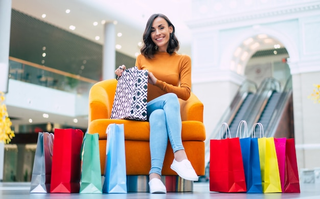 Mooie trendy jonge vrouw met veel kleurrijke boodschappentassen in goed humeur met slimme telefoon en creditcard zittend in het winkelcentrum tijdens zwarte vrijdag