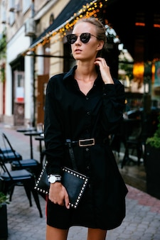 Mooie trendy vrouw in zonnebril, zwarte jas, met handtas dragen