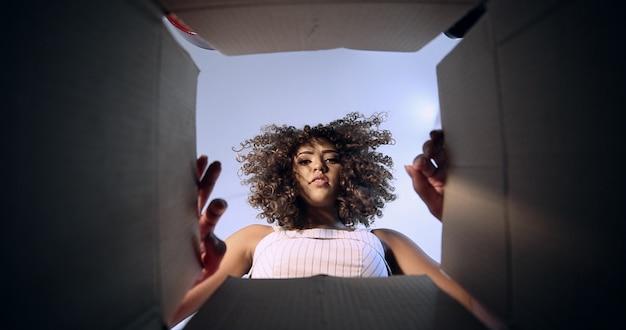 Mooie trieste brunette met krullend haar die de doos opent met uw bestelling die is ontvangen door het postkantoor of koeriersbedrijf. braziliaanse jonge vrouw die orde ontvangt.