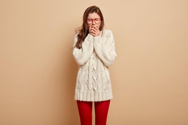 Mooie trieste vrouw lijdt aan pijn, depressief van verdriet, bedekt de mond, probeert te stoppen met huilen, lijdt aan kiespijn, draagt een witte trui met lange mouwen, heeft een ellendige gezichtsuitdrukking, staat binnen