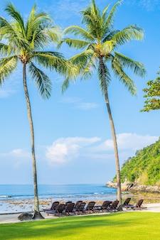 Mooie tropische kokospalm met stoel rond strand overzeese oceaan met witte wolk op blauwe hemel