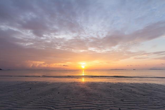 Mooie tropische paarse strandzonsondergang met kleurrijke overzeese hemel