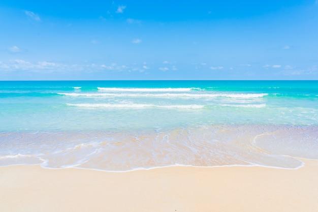 Mooie tropische strand zee oceaan met witte wolk en blauwe hemelachtergrond voor reizen vakantiereis