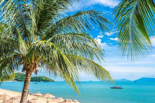 Mooie tropische strandoverzees en oceaan met kokospalm en paraplu en stoel op blauwe hemel