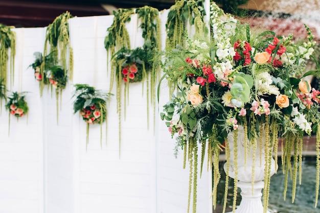 Mooie trouwfotozone in het park, een wit scherm, een voetstuk met bloemen en decor.