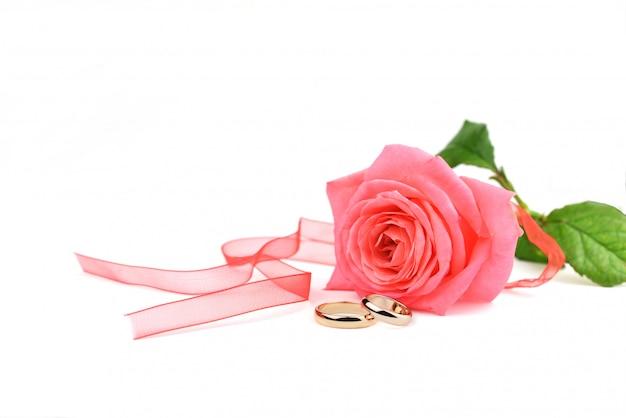 Mooie trouwringen goud voor pasgetrouwden met een roze roos