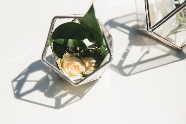Mooie trouwringen met verse bloemen in een glazen vat bij de huwelijksregistratie ter plaatse