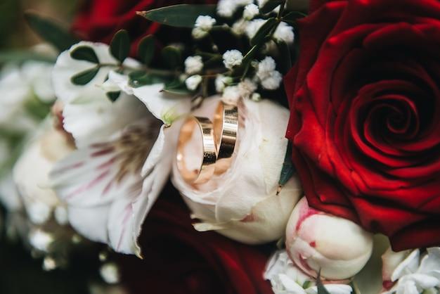 Mooie trouwringen op de achtergrond van het boeket van de bruid met rode en witte rozen