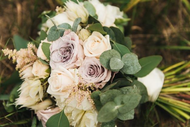 Mooie trouwringen op het boeket van de bruid in pastelkleuren