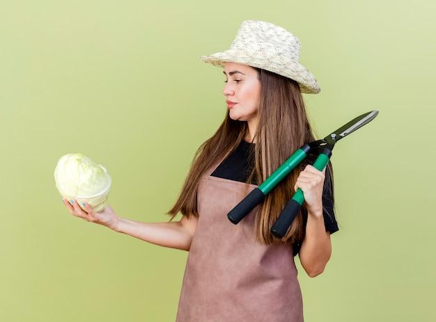 Mooie tuinman meisje denken in uniform dragen tuinieren hoed tondeuse op schouder zetten en kijken naar kool in haar hand geïsoleerd op olijfgroene achtergrond