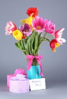 Mooie tulpen in boeket met cadeaus en notitie op grijs