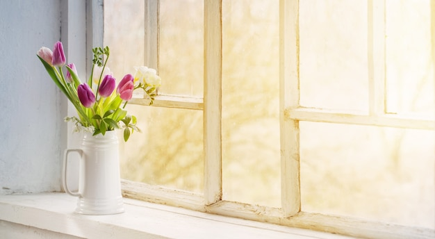 Mooie tulpen in kruik op oude witte vensterbank