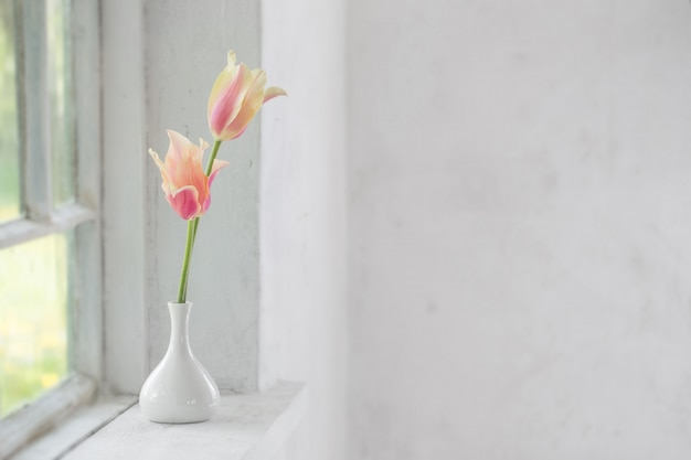 Mooie tulpen in vaas op witte vensterbank
