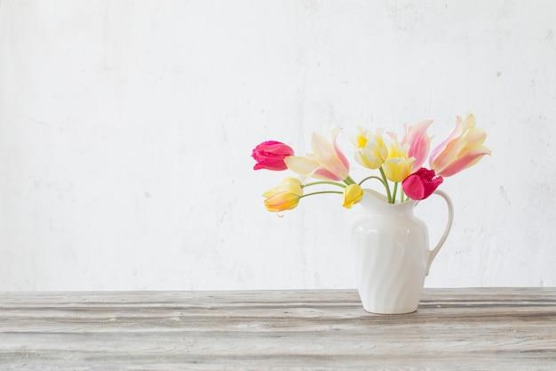 Mooie tulpen in witte kruik op houten tafel