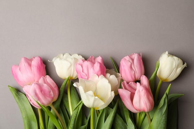 Mooie tulpen op grijze achtergrond, ruimte voor tekst