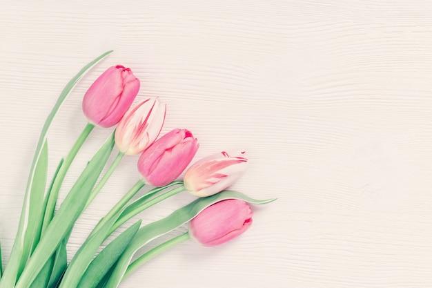 Mooie tulpen roze gekleurd op witte houten achtergrond met kopie ruimte