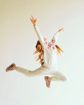 Mooie turnster meisje in grijze sportkleding uitvoerende kunst gymnastiek element springen doen split sprong...