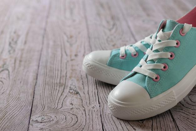 Mooie turquoise sneakers op de houten vloer.