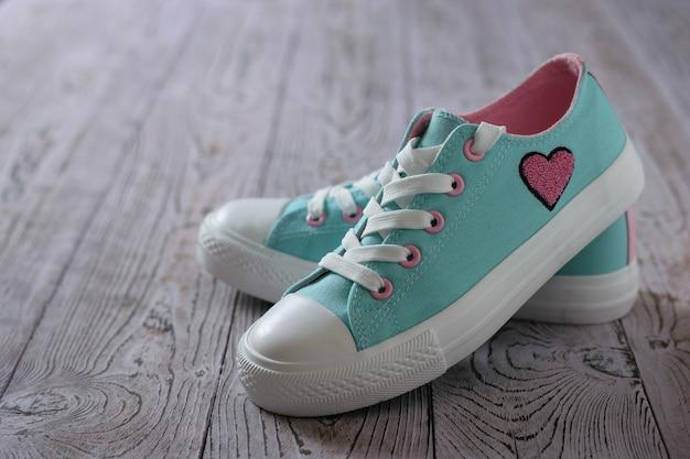 Mooie turquoise sneakers op een roze houten vloer.