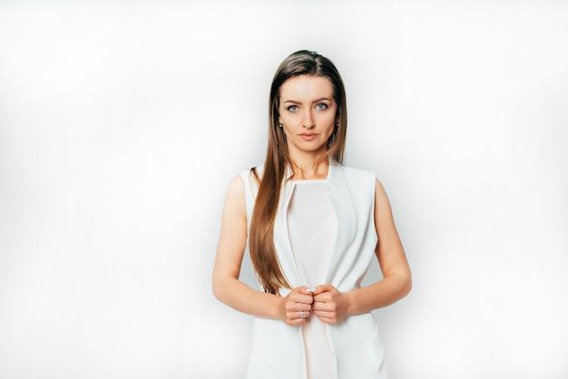 Mooie tv-presentator met lang haar staat in een wit pak in de studio
