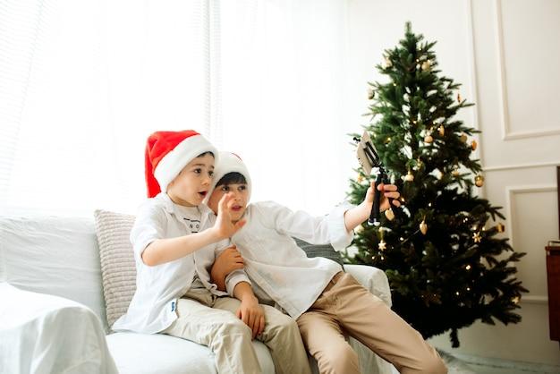 Mooie twee broers die thuis een selfie met mobiele telefoon nemen. gelukkige jonge geitjes die bij de kerstboom zitten.