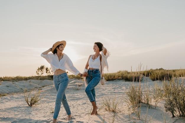 Mooie twee jonge vrouwen die plezier hebben op het zonsondergangstrand, homoseksuele lesbische liefde romantiek