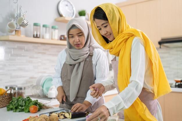 Mooie twee moslimvrouwen genieten van het samen koken van diner voor iftar die het vasten op ramadan in de keuken doorbreekt