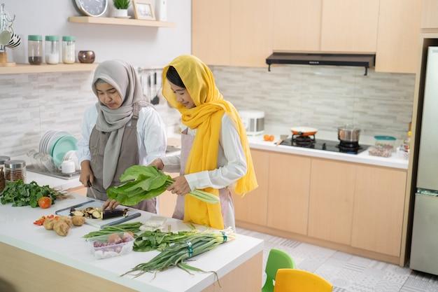 Mooie twee moslimvrouwen genieten van het samen koken van het diner voor iftar die het vasten verbreekt op ramadan in de keuken