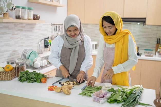 Mooie twee moslimvrouwen genieten van samen koken