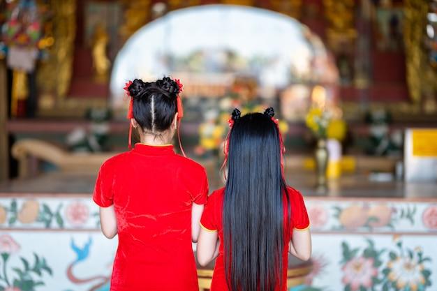 Mooie twee schattige kleine aziatische jonge vrouw dragen rode traditionele chinese cheongsam, staan voor bidden tot boeddhabeeld voor chinees nieuwjaar festival op chinees heiligdom