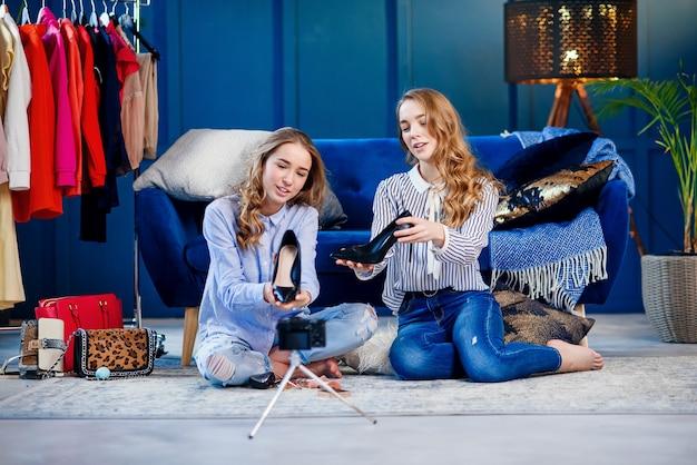 Mooie twee vrouwelijke bloggers die modieuze schoenen tonen aan de camera.