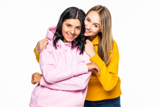 Mooie twee vrouwen die casual hoodies en jeans dragen, isoleerden een witte muur