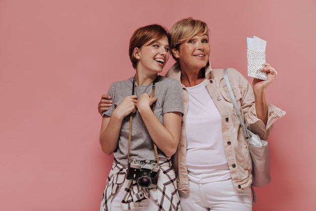 Mooie twee vrouwen met stijlvolle korte haarstijl in moderne kleding knuffelen, lachen en twee kaartjes en camera op roze achtergrond te houden.