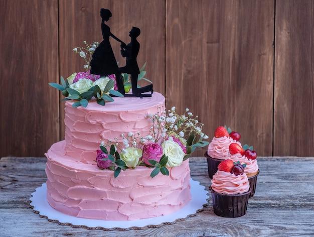 Mooie tweelaagse bruidstaart met roze kaascrème, versierd met levende rozen en een figuur van een verliefd stel, op een houten tafel met cupcakes