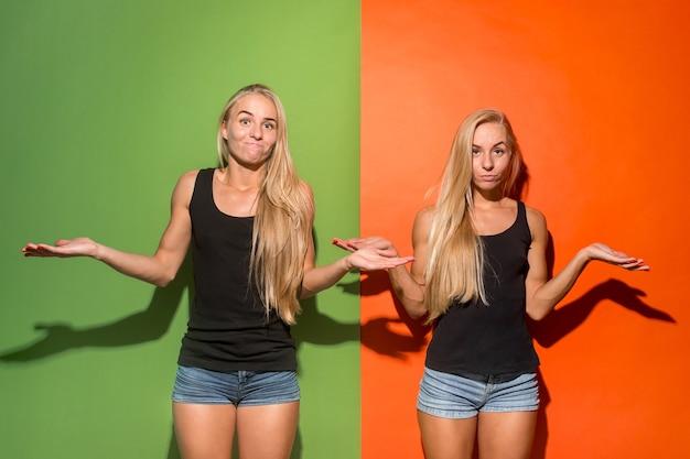 Mooie tweelingenvrouwen die gelukkig en ongelukkig op kleurrijke achtergrond kijken