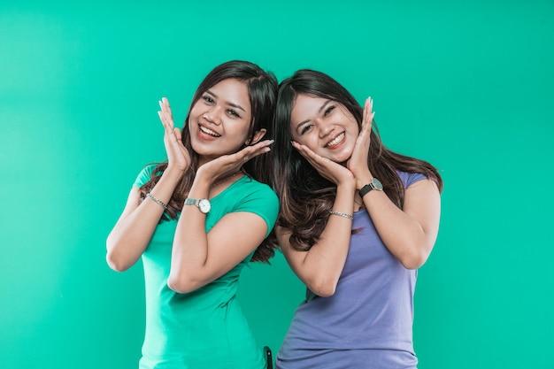 Mooie tweelingmeisjes heffen hun handen op hun kin op en glimlachen gelukkig samen, op groene achtergrond