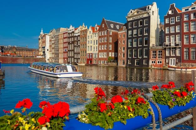 Mooie typisch nederlandse dansende huizen en toeristenboten bij het amsterdamse kanaal damrak in zonnige dag, holland, nederland.