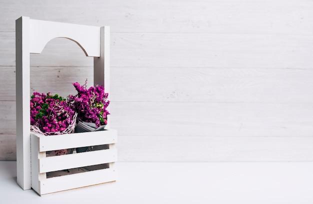 Mooie uiterst kleine purpere bloemen in kratten op bureau tegen houten achtergrond