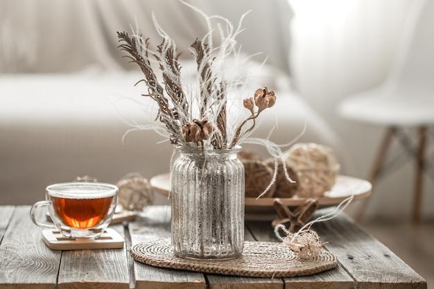 Mooie vaas met bloemen en een kopje thee