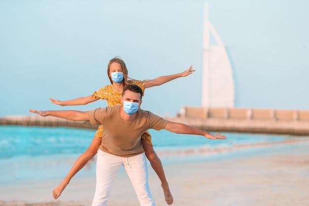 Mooie vader en dochter op het strand genieten van zomervakantie.