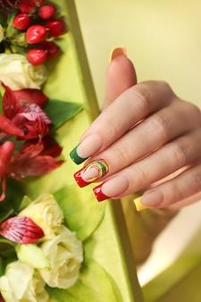 Mooie veelkleurige french manicure aan de hand van een vrouw met bloemen.