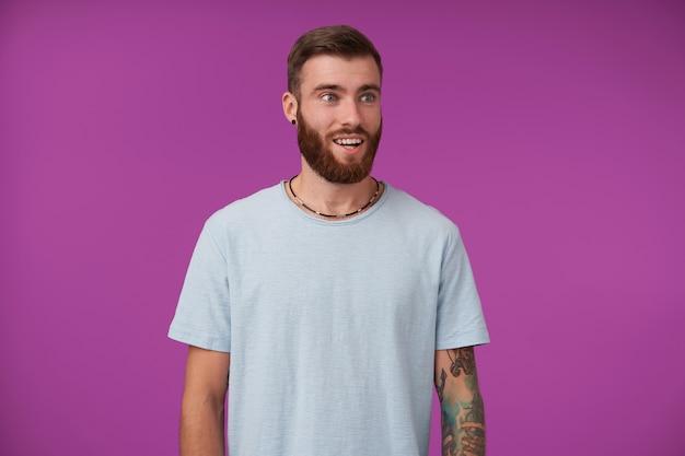 Mooie verbaasde jonge getatoeëerde man met baard die opzij kijkt met verbaasd gezicht en zijn perfecte witte tanden laat zien, vrijetijdskleding draagt terwijl hij op paars staat