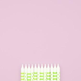 Mooie verjaardagskaarsen op roze achtergrond