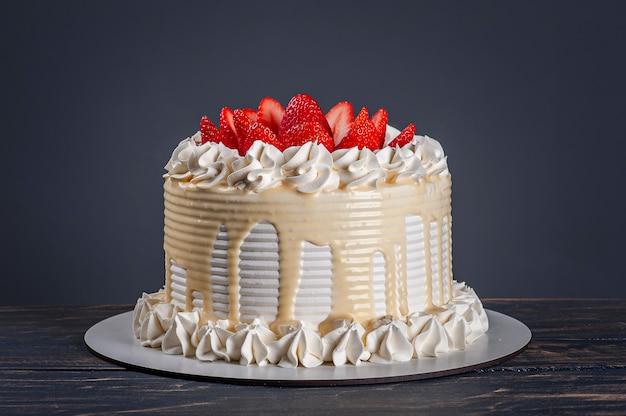 Mooie verjaardagstaart bedekt met chantilly en verse aardbeien. grijze achtergrond. ruimte kopiëren