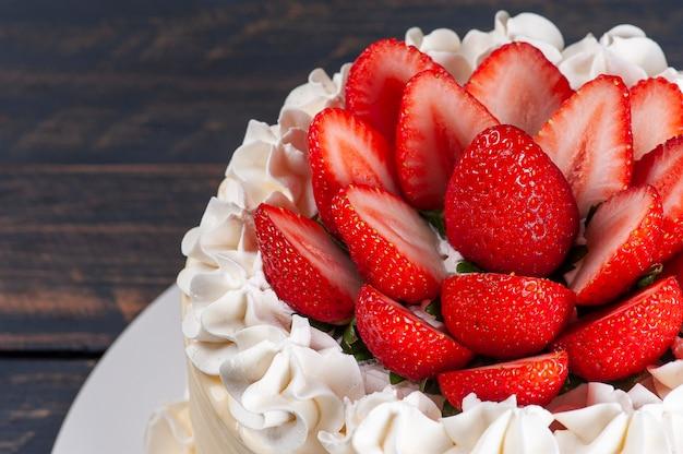 Mooie verjaardagstaart bedekt met chantilly en verse aardbeien. grijze achtergrond