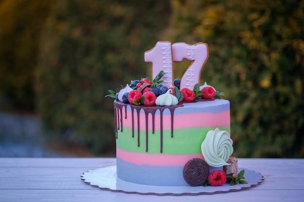 Mooie verjaardagstaart met het cijfer zeventien, versierd met verse bessen en kleurrijke room