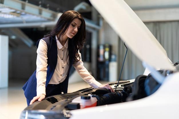 Mooie verkoop-kribbe inspecteert nieuwe auto in dealer showroom