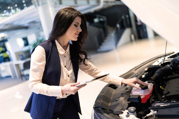 Mooie verkoop-kribbe inspecteert nieuwe auto met behulp van tablet in dealercentrum