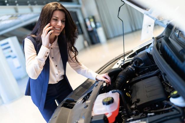 Mooie verkoopmanager inspecteert nieuwe auto en spreekt telefonisch in dealer showroom