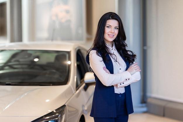 Mooie verkoopster die dichtbij nieuwe auto in dealercentrum bezit